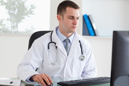 doctor computer: Young doctor working on his computer