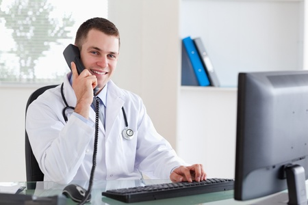 Smiling young doctor on the telephone photo