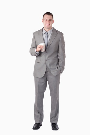 Portrait of a businessman holding a cup of tea against a white background photo