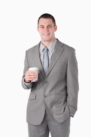 Portrait of a young businessman holding a cup of tea against a white background photo