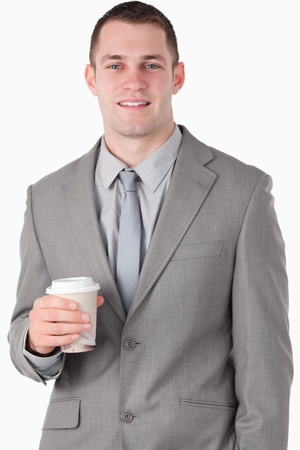 Portrait of a handsome businessman holding a cup of tea against a white background photo