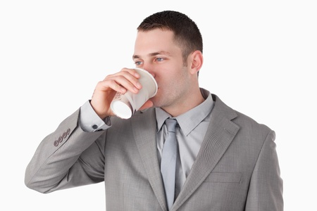 Businessman drinking tea against a white background photo