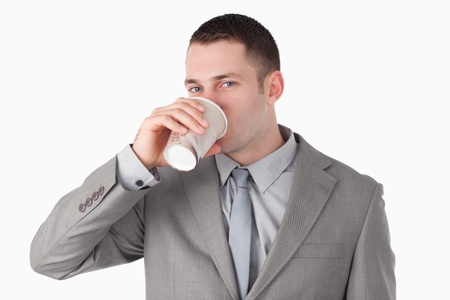 Businessman drinking coffee against a white background photo