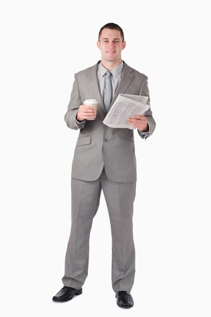 Portrait of a businessman holding a newspaper and a cup of coffee against a white background Stock Photo