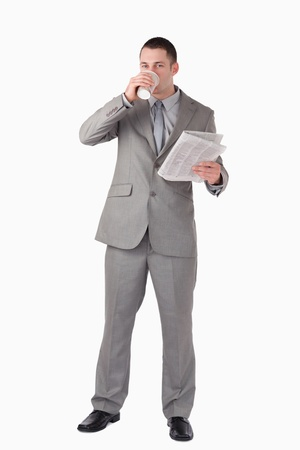 Portrait of a businessman holding a newspaper while drinking coffee against a white background photo