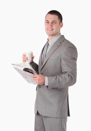 Portrait of a businessman holding a newspaper and a cup of tea against a white background photo