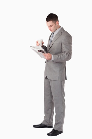 Portrait of a businessman holding a cup of tea while reading the news against a white background photo