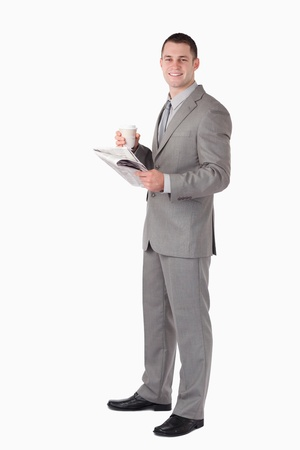 Portrait of a businessman holding a cup of coffee while reading the news against a white background photo