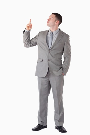 Portrait of a businessman pointing at a blank space against a white background