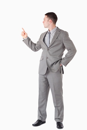 Portrait of a businessman pointing at something against a white background photo
