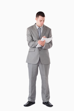 Portrait of a businessman taking notes against a white background photo