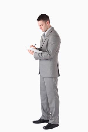 Portrait einer schweren Gesch�ftsmann sich Notizen vor einem wei�en Hintergrund