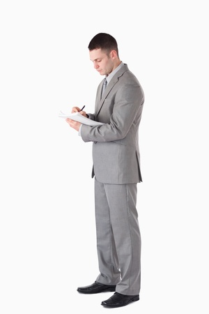 Portrait of a serious businessman taking notes against a white background photo