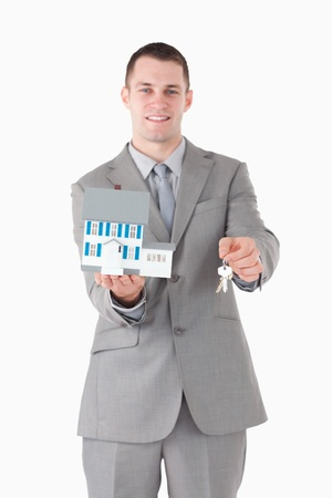 Portrait of a businessman holding a miniature house and keys against a white background