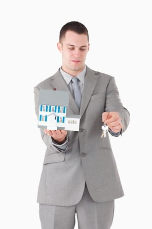Portrait of a businessman showing a miniature house and keys against a white background photo