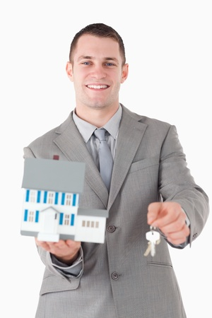 Portrait of a young businessman showing a miniature house and keys against a white background photo
