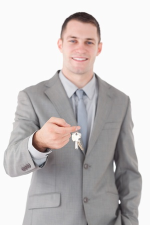 Portrait of a young businessman showing a set of keys against a white background photo