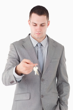 Portrait of a young businessman looking at a set of keys against a white background photo