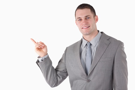 Young businessman pointing at something against a white background