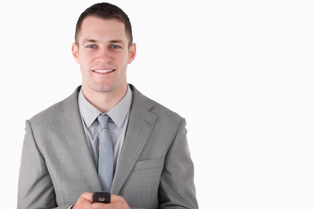 Businessman holding his cellphone against a white background photo