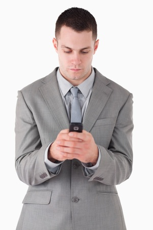Portrait of a businessman dialing on his cellphone against a white background photo