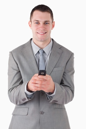 Portrait of a businessman holding his cellphone against a white background photo