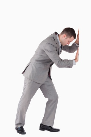 Portrait of a businessman pushing a wall against a white background photo