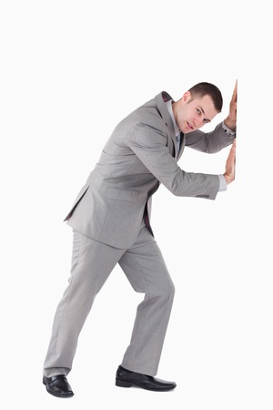 Portrait of a young businessman pushing a wall against a white background