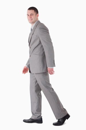 Portrait of a smiling businessman walking against a white background photo