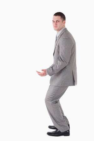 knees bent: Portrait of a young businessman carrying something against a white background Stock Photo