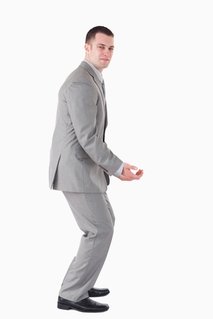 knees bent: Portrait of a handsome young businessman carrying something against a white background