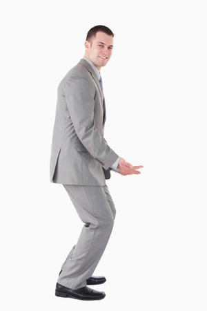 knees bent: Portrait of a smiling businessman carrying something against a white background