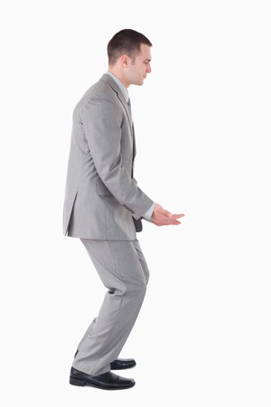 knees bent: Portrait of a businessman carrying something heavy against a white background Stock Photo
