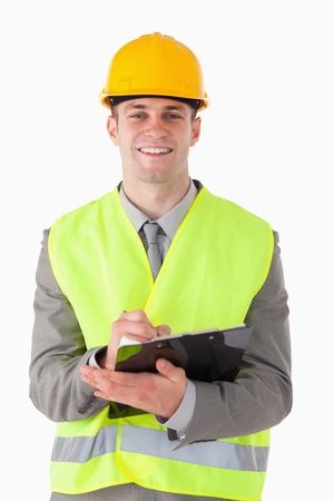 Portrait of a smiling builder taking notes while smiling at the camera photo