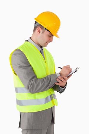Portret van een bouwer het maken van aantekeningen tegen een witte achtergrond