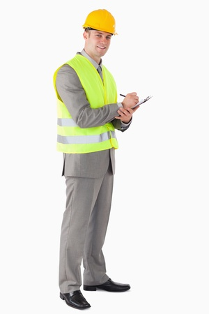 Portrait of a smiling contractor taking notes against a white background photo