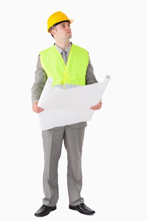 Portrait of an architect holding a plan while looking around against a white background photo