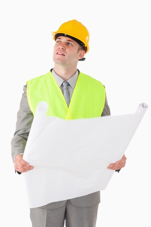 Portrait of a builder looking around while holding a plan against a white background photo