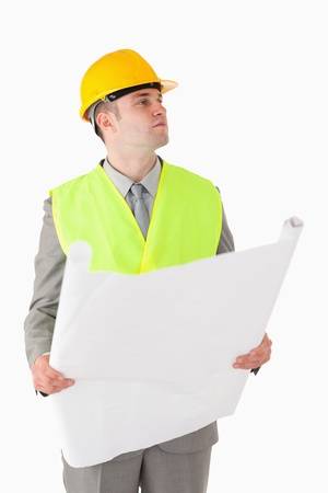 Portrait of a young builder looking around while holding a plan against a white background Stock Photo
