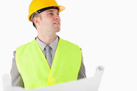 Builder holding a plan while looking around against a white background photo