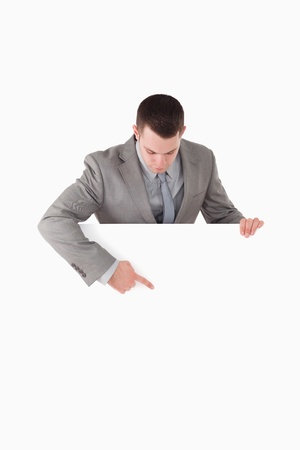 Portrait of a businessman pointing at something on a panel against a white background Stock Photo - 11618713