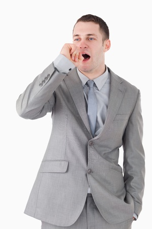 Portrait of a businessman yawning against a white background photo