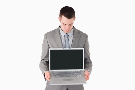 Businessman showing a laptop against a white background Stock Photo