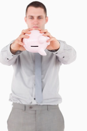Portrait of a businessman shaking a piggy bank against a white background photo