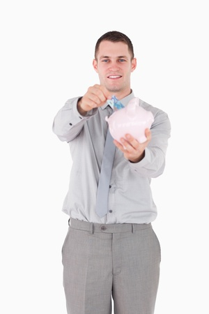 Portrait of a young businessman putting a note in a piggy bank against a white background photo