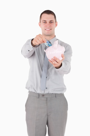 Portrait of a businessman putting a note in a piggy bank against a white background photo