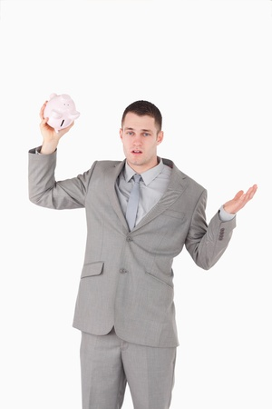 Portrait of a broke businessman shaking an empty piggy bank against a white background photo