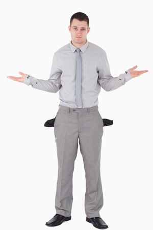 moneyless: Portrait of a young businessman with empty pockets against a white background