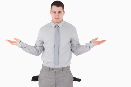 moneyless: Businessman with empty pockets against a white background
