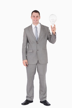 Portrait of a businessman holding a bulb against white background photo